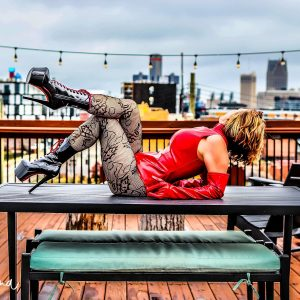 Detroit Dominatrix in red latex on table outside