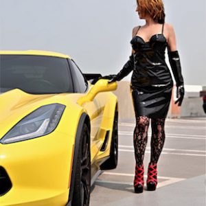 Detroit Domme in PVC next to yellow sports car