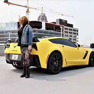 Woman in denim in front of yellow corvette